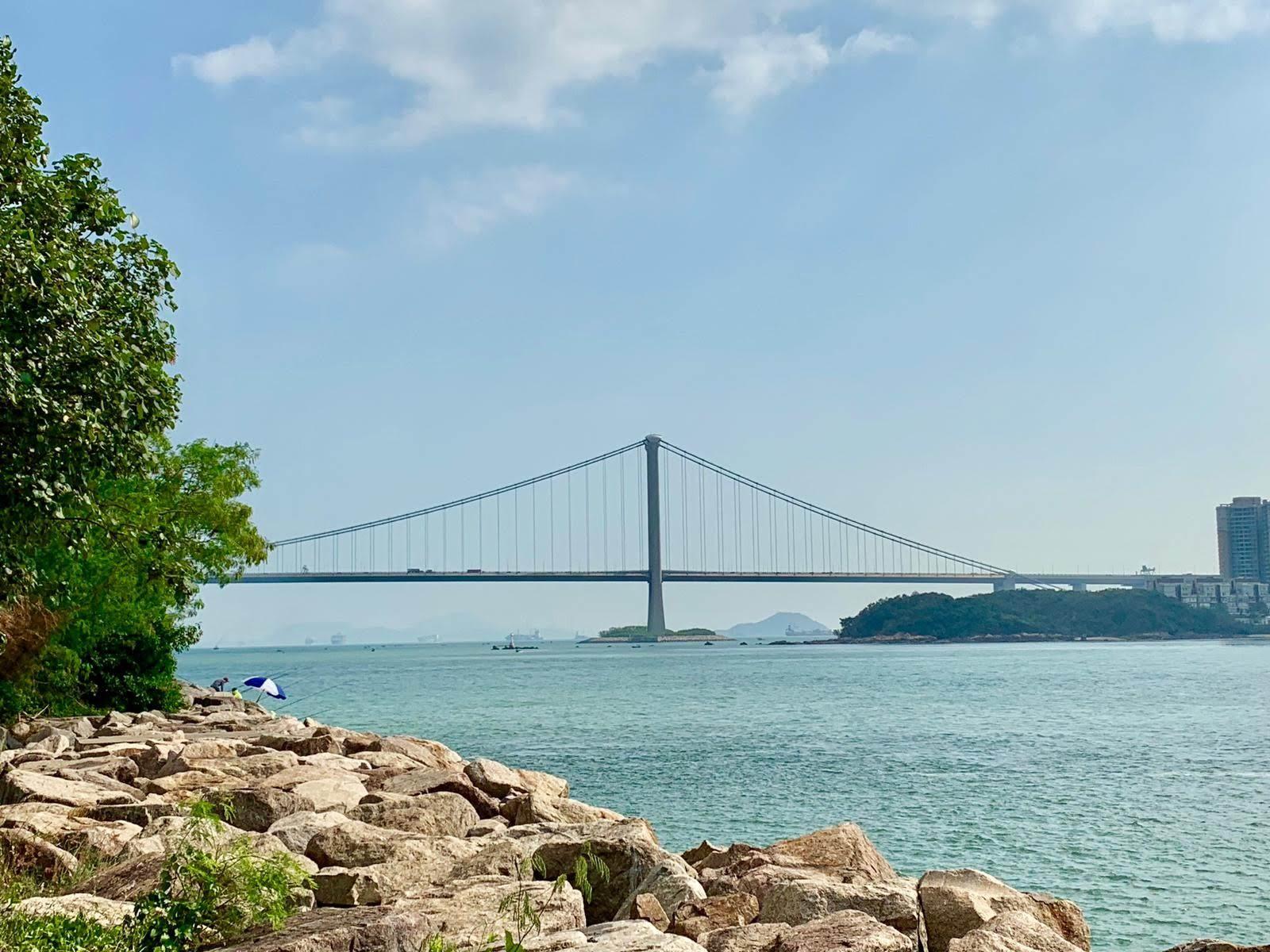 blue sky, long bridge, sea, rocky shore