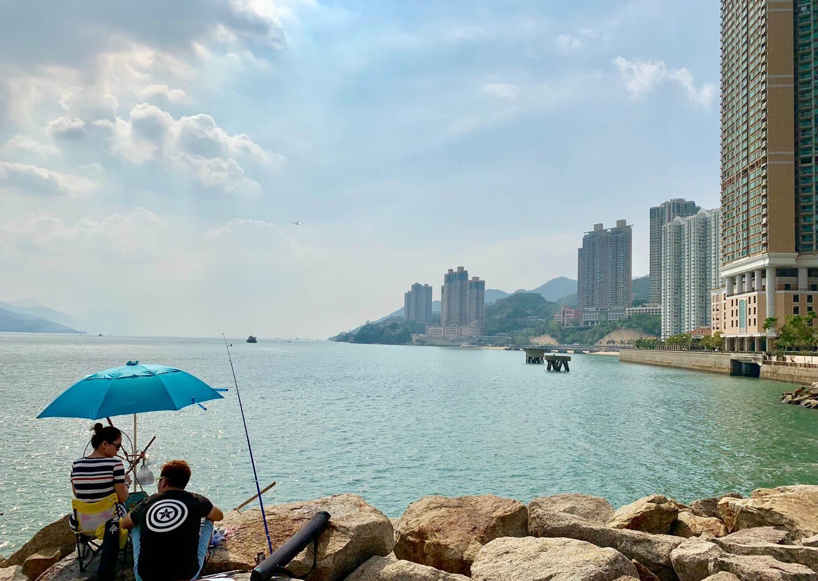 anglers under unbrella, sea, buildings on shoreline
